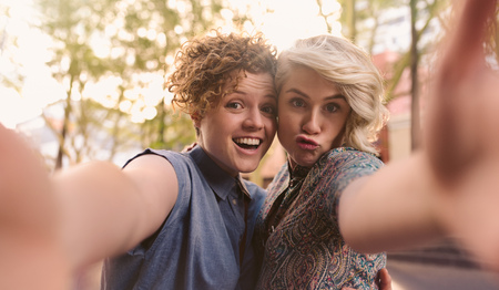 Smiling  couple making faces and taking selfies together outside Stock Photo
