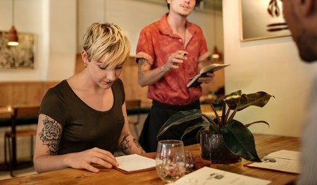 Woman reading the menu while sitting at a bistro table