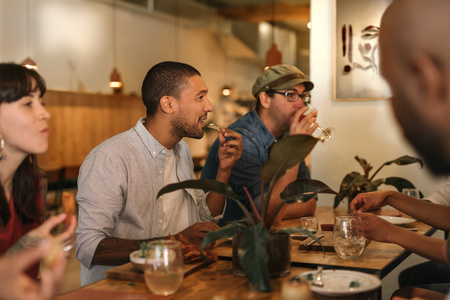 Smiling young friends enjoying dinner together in a trendy bistro Stockfoto