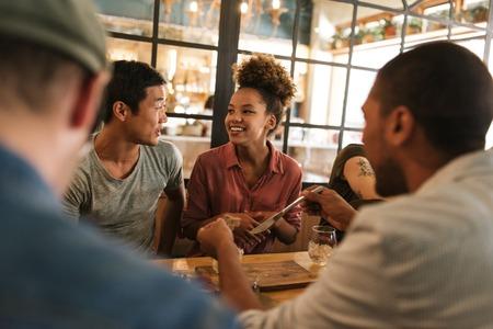Sonriendo a jóvenes amigos hablando juntos durante una cena bistro