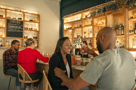 Smiling African American couple enjoying drinks together in a bar Imagens