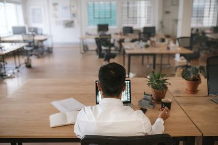 Geschäftsmann arbeitet allein an seinem Schreibtisch in einem Büro