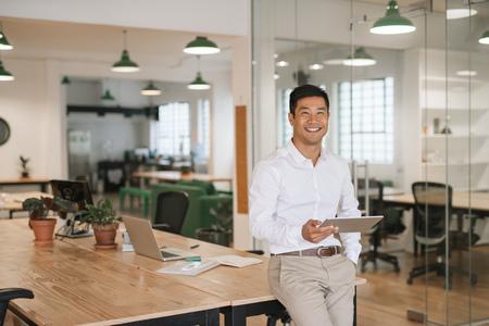 Lächelnder asiatischer Geschäftsmann, der eine Tablette in einem Büro verwendet