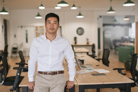 Confident Asian businessman leaning on a desk in an office