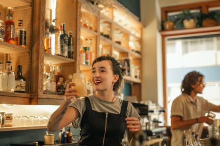 Smiling young female bartender making cocktails in a bar Stock Photo