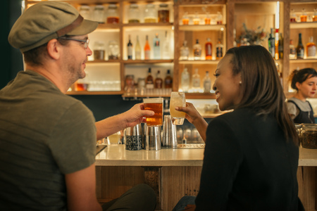 Two smiling friends sitting in a bar cheering with drinks