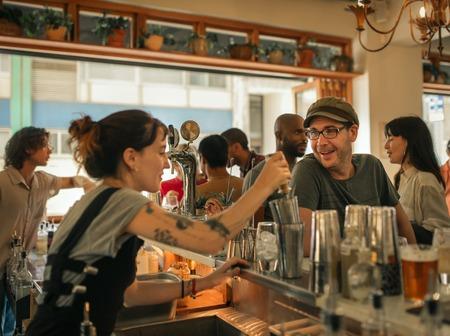 Lächelnder Gönner, der Getränke in einer trendigen Bar bestellt Standard-Bild
