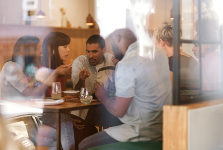 Diverse group of young friends eating together in a bistro