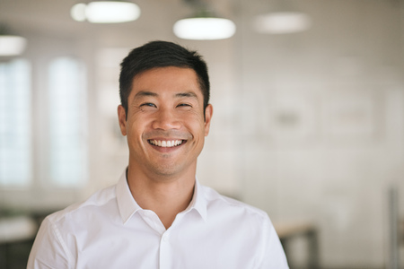 Young Asian businessman standing in an office smiling confidently Stock Photo