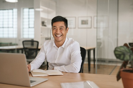 Smiling young Asian businessman working at his office desk 写真素材