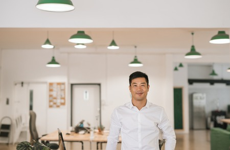 Young Asian businessman smiling confidently while standing in an office Imagens