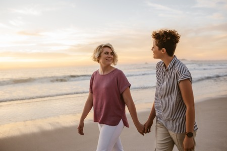 Smiling lesbian couple walking along a beach at sunset Stockfoto