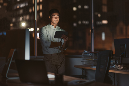 Asian businessman working late in his office with a tablet