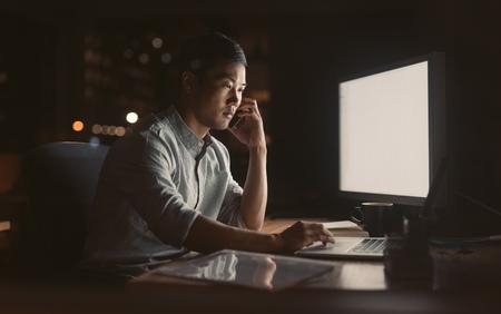 Empresario asiático hablando por su teléfono celular en una oficina oscura