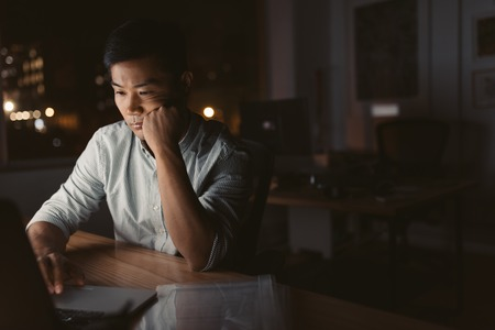 Tired Asian businessman working at his desk late at night