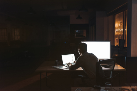 Businessman working overtime at his desk late at night Banco de Imagens