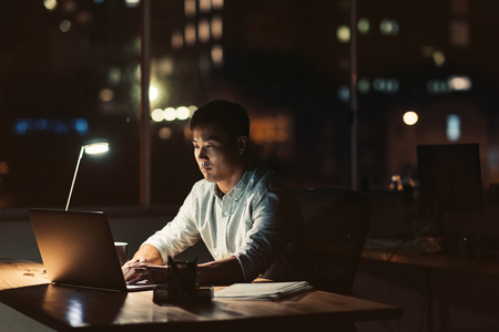 Young Asian businessman working late at night at his desk Banque d'images
