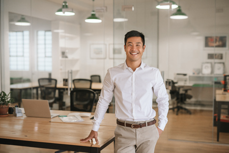 Young Asian businessman standing in an office smiling confidently Stockfoto