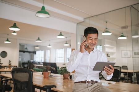 Asiatischer Geschäftsmann, der auf seinem Handy spricht und eine Tablette hält