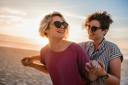Laughing lesbian couple dancing playfully on a beach at sunset Stock fotó
