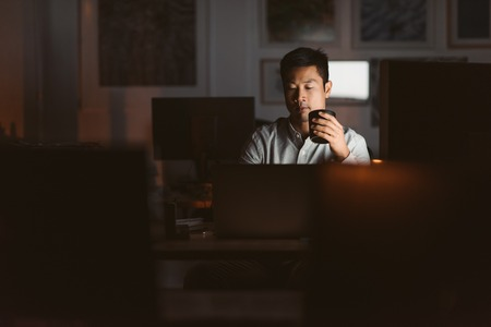 Asian businessman drinking coffee while working late in an offic