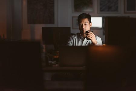 Uomo d'affari asiatico che beve caffè mentre lavora fino a tardi in un offic