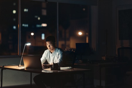 Young Asian businessman working on a laptop while sitting at his desk in a dark office at night with city lights in the background