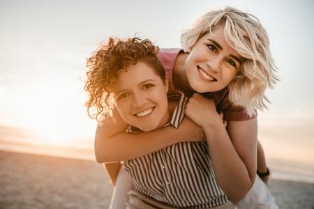 Jonge vrouw geeft haar vriendin een ritje op de rug op het strand