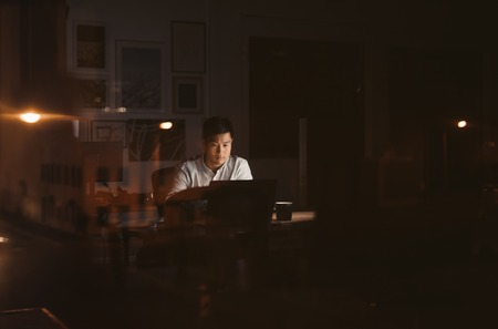 Young Asian businessman working overtime alone in a dark office