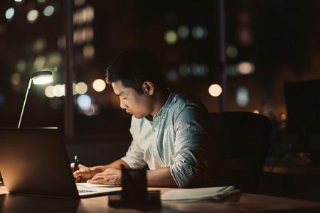 Asiatischer Geschäftsmann, der bis spät in den Abend an seinem Schreibtisch arbeitet