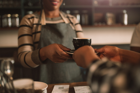 Smiling African barista giving her customer a fresh cappuccino