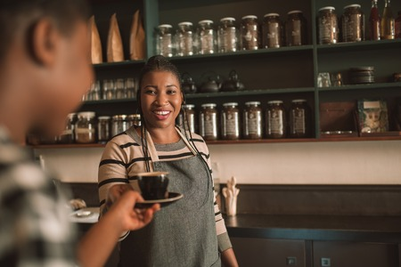 Smiling young African barista giving her customer a cappuccino