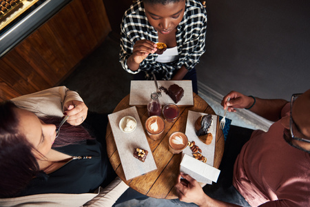 Friends sitting at a cafe table enjoying delicious desserts together Stockfoto
