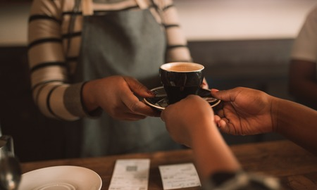 Closeup of an African barista giving a customer her cappuccino