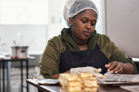 Worker wrapping molded chocolate bars in gold foil packaging Foto de archivo - 111147557