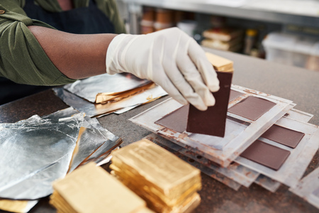 Worker wrapping chocolate bars from molds in gold foil
