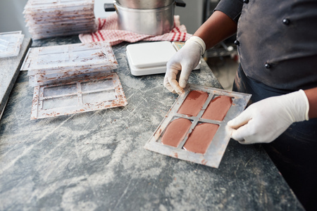Worker holding a bar mold full of melted chocolate Foto de archivo - 114884280