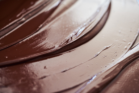 Glistening melted chocolate spread out on a table