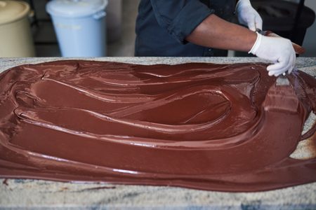 Worker spreading chocolate out with spatulas on a factory table Imagens