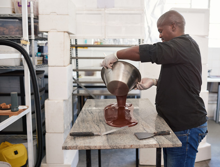 Worker pouring melted artisanal chocolate out on a factory table