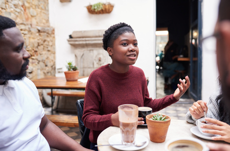 Young woman talking with friends in a trendy cafe courtyard Stock Photo