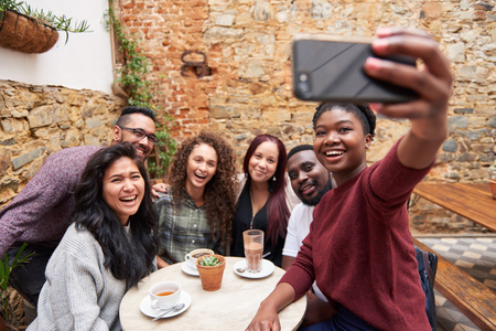 Smiling young friends taking selfies together in a cafe courtyard
