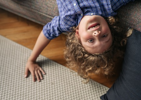 Little boy hanging upside down from his living room sofa