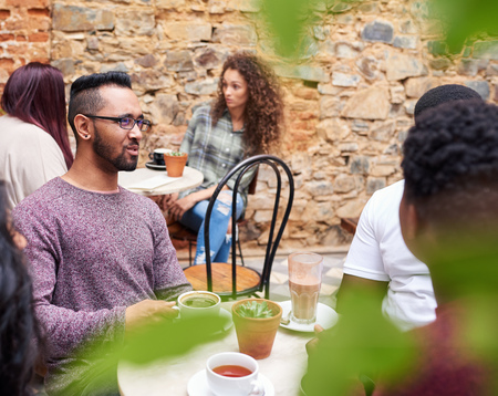 Young man talking with friends in a trendy cafe courtyard