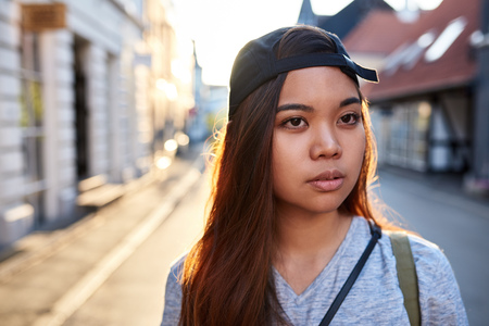 Stylish young Asian woman walking through city streets