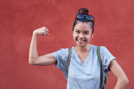 Young Asian woman smiling while humorously flexing her bicep outside Stock fotó