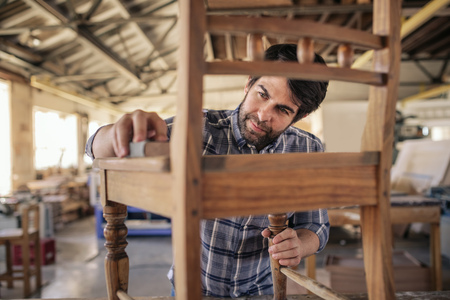 Furniture maker skillfully sanding a chair in his workshop