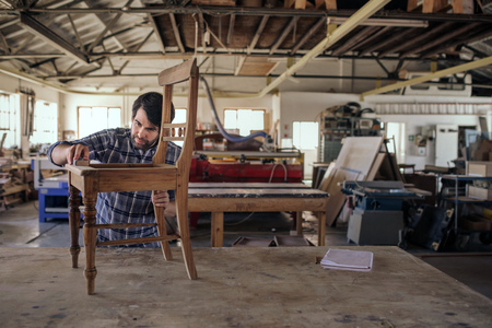 Woodworker sanding a chair on his workshop table