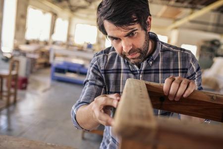Fabricant de meubles travaillant sur une chaise dans son grand atelier Banque d'images