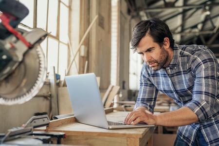 Holzarbeiter recherchiert am Laptop in seiner Werkstatt